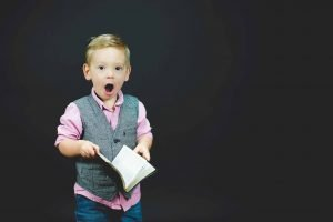 a little boy holding a book with his mouth wide open